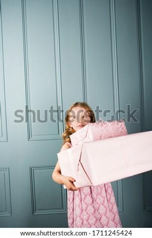 little girl carrying presents in front of a door way