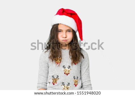 Little girl celebrating christmas day blows cheeks, has tired expression. Facial expression concept.