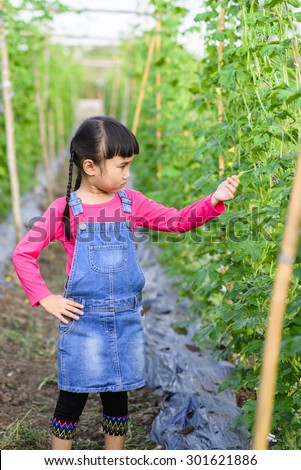 Little girl check product in the garden after plantation for one month