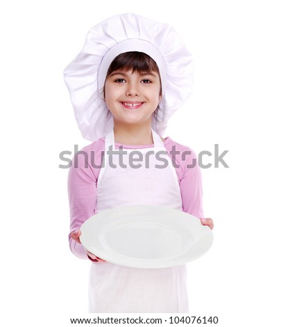 Little girl chef holding the white plate