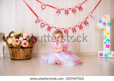 Little girl child celebrate first Happy Birthday Party in pink dress with  decor in the beautiful room