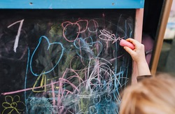 Little girl, child draws with colored chalk on a black wooden board drawing, doodle. The educational process of drawing at school.