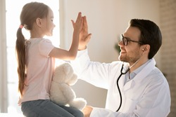 Little girl child give high five greeting with positive male doctor or GP at consultation in clinic, small kid make deal celebrate good medical checkup with smiling pediatrician at meeting in hospital