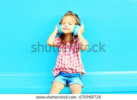little girl child listens to music in headphones on a colorful blue background #670988728
