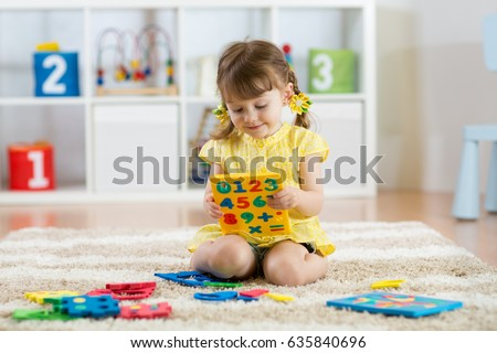 Little girl child playing with lots of colorful plastic digits or numbers on floor indoors.
