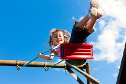 Little girl child sitting on a swing in the garden playground; she has lots of fun