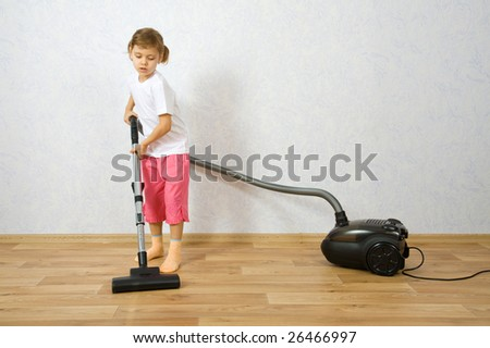 Little girl cleaning floor with vacuum cleaner