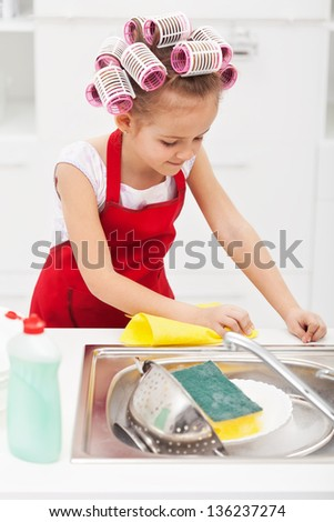 Little girl cleaning the kitchen - wiping the sink area, wearing big hair curls