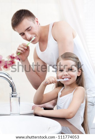 Little girl cleans her teeth with her father in bathroom