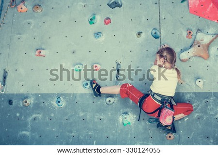little girl climbing a rock wall indoor #330124055