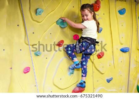 little girl climbing a rock wall indoor #675321490