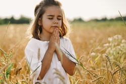 Little Girl closed her eyes, praying in a field wheat. Hands folded in prayer. Religion concept
