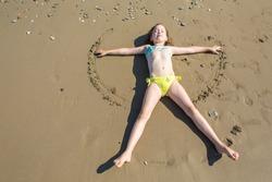 Little girl, closing her eyes, making sand angel on beach of Belek in Turkey