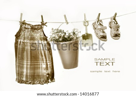 Little girl clothes and toys on a clothesline against white background/ Sepia tone - stock photo