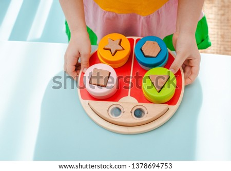 little girl collects wooden multi-colored sorter Safe natural wooden kids toys Educational game #1378694753