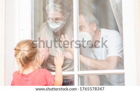 Little girl communicates with his grandparents through a window during the coronavirus epidemic