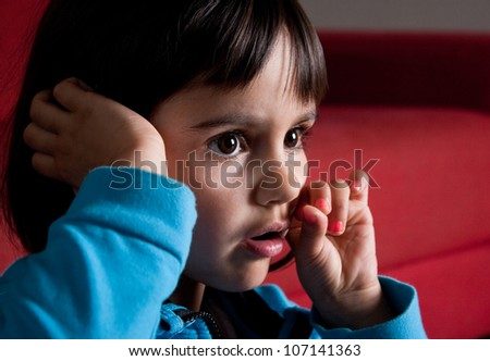 little girl concentrated watching tv alone with the eyes and mouth opened