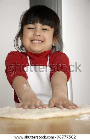 Little girl cooking a pizza in a kitchen.Little kid in a kitchen.