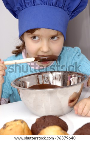 Little girl cooking chocolate in a kitchen.Little girl using a chef cap and cooking in a kitchen.