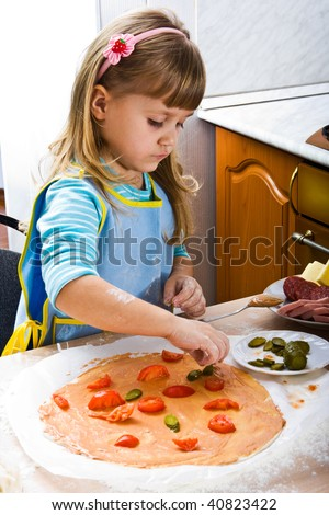 Little girl cooking pizza on the kitchen