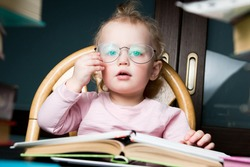 Little girl corrects adult glasses of her mother on her face. Child playing student
