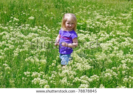 Little girl costs in a grass outdoors smiling