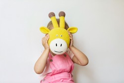 Little girl covered her face with a giraffe head toy
