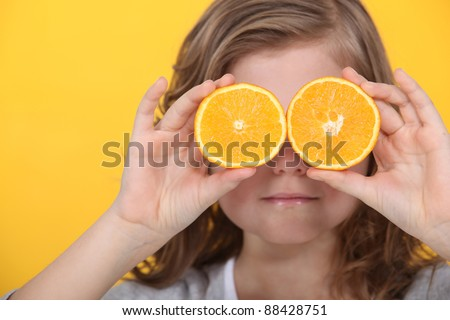 Little girl covering eyes with slices of orange