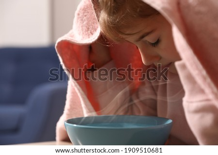 Little girl covering head with towel and inhaling steam indoors, closeup Stock photo ©