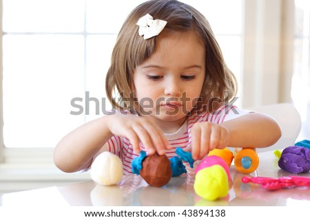 Little girl creating toys from play dough