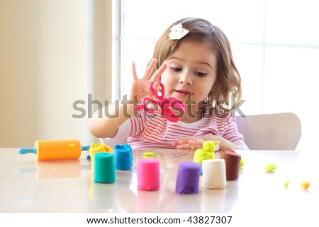 Little girl creating toys from playdough