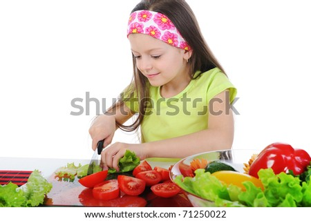 little girl cut fresh tomatoes. Isolated on white background