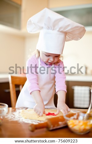 Little girl cuts dough for cookies on kitchen with form