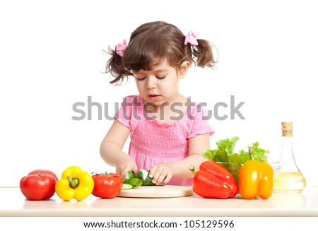 Little girl cutting vegetable for salad. Concept of healthy food.