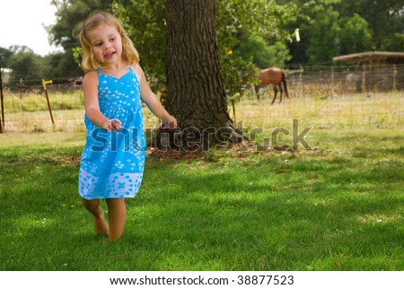 Little girl dancing in the grass at a horse farm