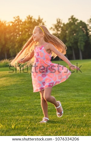 Stock Photo Little girl dancing, summer. Child on nature background. The energy of life.