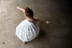 Little girl dancing twirling in white dress.