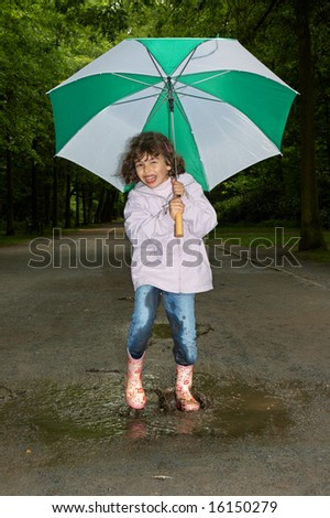 Little girl dancing with her umbrella in a water puddle - stock photo