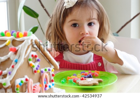 Little girl decorating gingerbread house and treating herself to candy