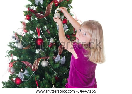Little girl decorating the Christmas tree