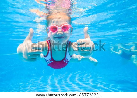 little girl deftly swim underwater in pool