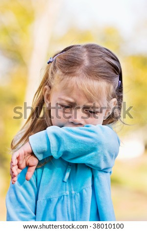 Little girl demonstrates coughing or sneezing into her sleeve to avoid spreading unwanted germs.