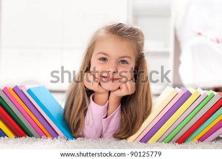 Little girl discovering the colorful world of books and knowledge