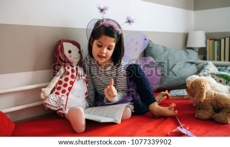 Little girl disguised as a butterfly sitting on the bed reading a book to her rag doll