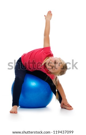 Little girl doing fitness exercise with gym ball. Studio shot.