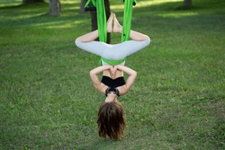 Little girl doing yoga exercises with a hammock in the park