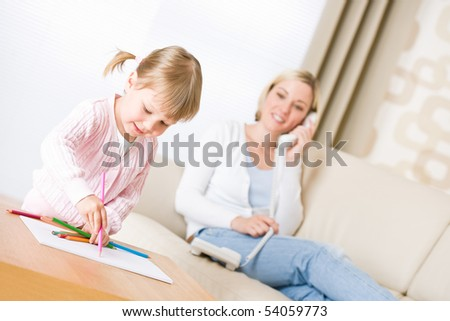 Little girl draw with color pencil in lounge, mother with phone calling in background