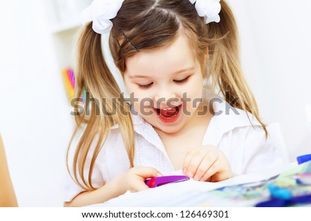 Little girl drawing and studying at home