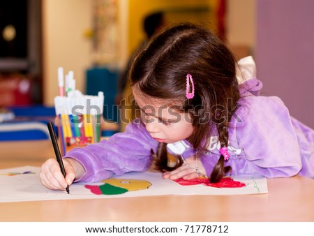 Little girl drawing concentratedly in a kindergarten