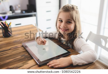 Little Girl Drawing Digital Picture on Electronic Tablet with Stylus Pen